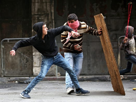 Palestinian protesters throw stones at Israeli soldiers