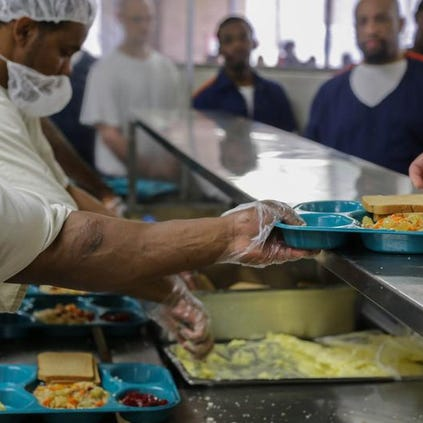 Inmates are served food by Aramark Correctional Services workers on Tuesday, June 24, 2014, at the Egeler center in Jackson.
