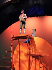 James (Carl Kimbrough) sings from atop a giant peach