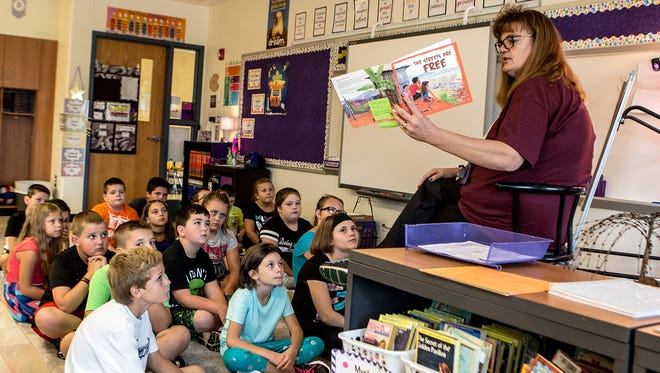 Laura Fischer reads a book to her 4th grade students on the first day of school at Carson Elementary. It was also Fischer's first day as a full-time teacher. After subbing for five years and going back to school in her 40s Fischer decided the time was right to follow her dreams of being a teacher in the school district she loves.