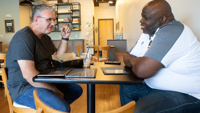 The Rev. Grant English, left, pastor of Western Hills Church, talks with the Rev. T.D. Hicks, right, of Antioch Missionary Baptist Church, on Friday afternoon at Dialogue Coffee. Conversations with various religion leaders in town have been ongoing to better understand each other and relate.