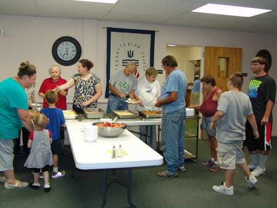 Volunteers serve guests at the Coshocton Presbyterian Church's community meal held earlier this month..