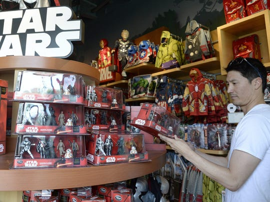 """767080187918 A man looks at """"Star Wars"""" toys at the Disney Store"""