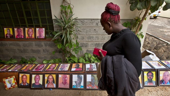 A morgue worker observes a row of photographs of some of those killed in the Garissa attack, which families were asked to bring to accompany the bodies after they are released for burial, at the Chiromo Funeral Parlour in Nairobi, Kenya Thursday, April 9, 2015. A week after the attack by extremist group al-Shabab on Garissa University College, relatives of the deceased continued their wait Thursday for the bodies to be released, hoping to be able to arrange their burials. (AP Photo/Ben Curtis)