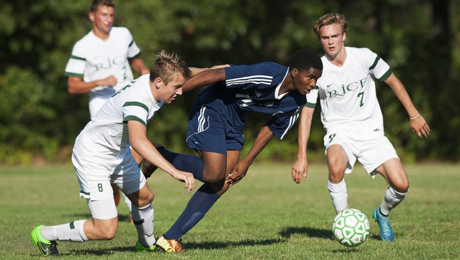 Burlington's Peter Makuni (14) runs between Rice's Evan Rouleau (7) and Loius Gazo (8) with the ball during a high school boys soccer game earlier this season.