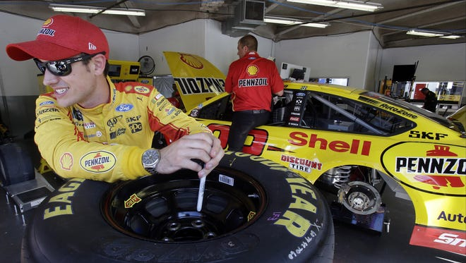 Joey Logano, left, takes a break in his garage while crew members make adjustment to his car during a NASCAR cup auto racing practice at Daytona International Speedway on Thursday.