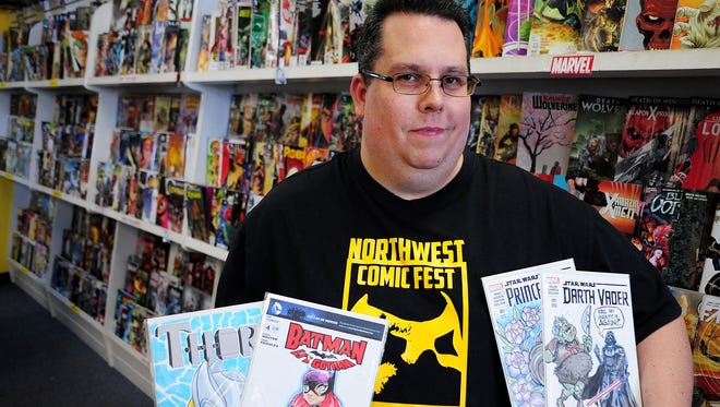 John Rogers, seen at Tony's Kingdom of Comics in Keizer, shows off some of the donated artwork for Comic Book Covers 4 Cancer.