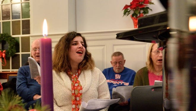Bergen; Oakland 12/20/2015 Sandy Khabbazeh of The Ponds Reformed Church in Oakland, center, sings with church members at a caroling event on Sunday night.