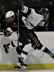 Plymouth's Graham Sheehan (right) and Canton's Brett Cygan collide at the boards Wednesday at Arctic Edge Arena.
