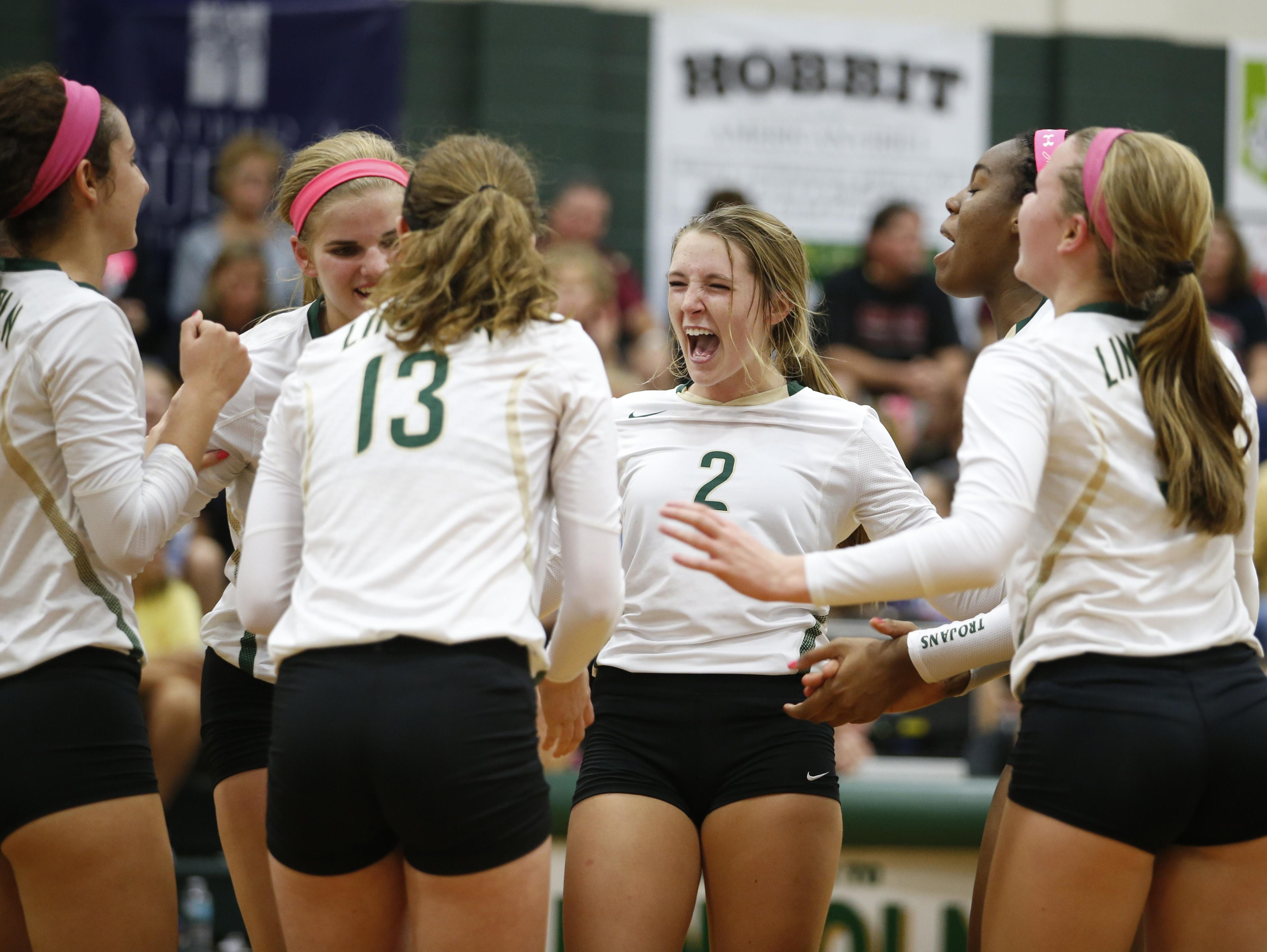 Lincoln's Callie Workman celebrates with teammates after scoring a point against Chiles during their match at Lincoln on Tuesday. The Trojans won 3-2 in an important district game.