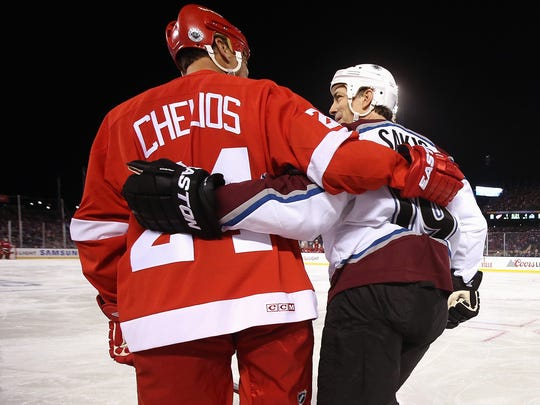 Red Wings defenseman Chris Chelios and Avalanche forward Joe Sakic skate across the ice during the 2016 Coors Light Stadium Series Alumni Game at Coors Field on Friday.