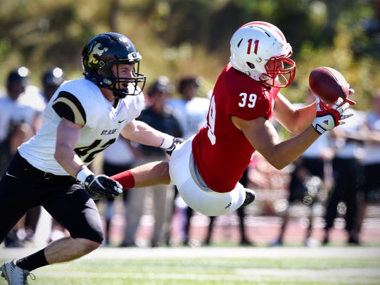 Tommy Auger leaps to make a catch for St. John's University during the Saturday, Sept. 17 game against St. Olaf at Clemens Stadium in Collegeville.