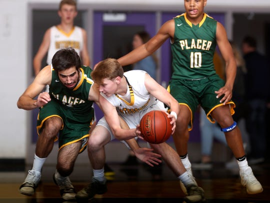 Enterprise's Tyler Hafner fights for possession of the ball with Placer's Derek Shreeve, left, Thursday during the Hornets' 68-49 loss to Placer on the opening night of the 2017 Harlan Carter Invitational.