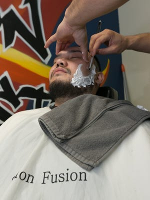 "Reynaldo ""Artsy"" Tingson stylist gets his facial hair shaved by Joe Blas, licensed barber at Salon Fusion. The new trends in facial hair styles have gotten more men heading to the barbershop to keep their look on point."