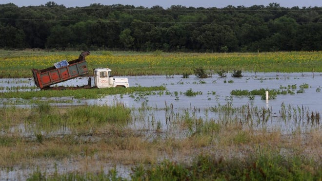 Ronald W. Erdrich/Reporter-News A dump truck with its bed raised is surrounded by floodwaters June 3 along FM 2214 north of Desdemona.