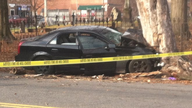 A black Cadillac CTS smashed head-on into a tree on South Street in the City of Newburgh on December 11, 2015.  Police said gang members were fleeing gunshots when they lost control of the car and crashed.    LEONARD SPARKS/TIMES HERALD-RECORD