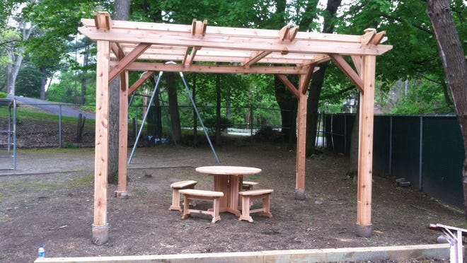 """A pergola, table and benches were constructed to make a """"conversations area"""" for the Grace Smith House."""