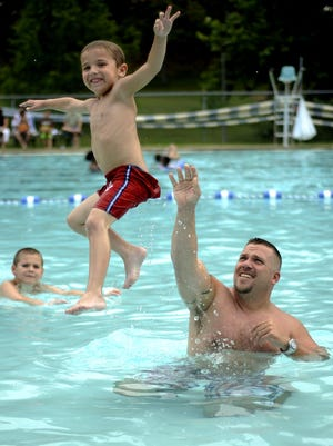 Greg Kauffman throws his son, Greg Jr., into Gypsy Hill Park pool.