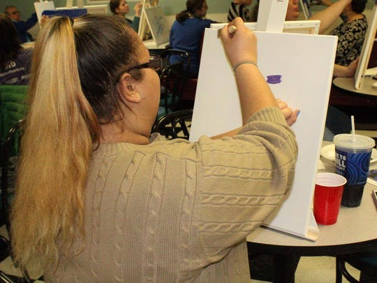 A Support Circles member participates in a paint night activity during a meeting the evening of April 6.