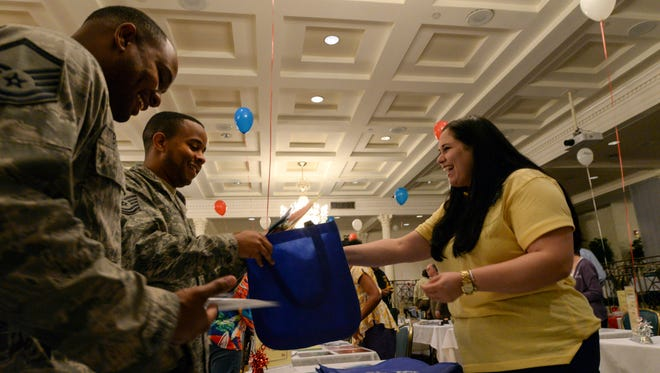 Master Sgt. Shaylor Bernard, Jeanne Holm Center Support Directory superintendent, left, and Tech. Sgt. Jason Becoat, 42nd Air Base Wing Ground Safety non-commissioned officer in charge, right, gather information from Cydney Hartner, Food For The Poor, Inc. program specialist, about the services the organization provides during the 2015 Combined Federal Campaign kickoff event Sept. 22, held at Maxwell Air Force Base. Food for the Poor provides food, medicine and shelter to the poor in Latin America and the Caribbean.