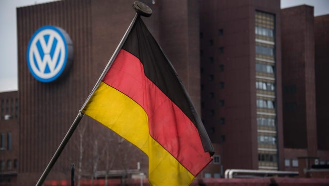 This picture shows a German flag on a boat with the Volkswagen HQ plant in the background, in Wolfsburg, Germany, on March 7, 2016.