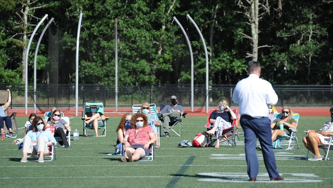 """Standing at the 50-yard line of the Monomoy Regional High School football field, district Superintendent Scott Carpenter speaks to a group of teachers Monday during their annual meeting before the start of the school year. """"Welcome back to Part II of the strangest year of our professional careers,"""" he told them."""