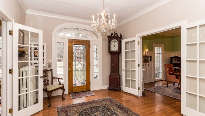 Crown molding, hardwood floors and original glass in the windows and doors can be seen in the foyer.