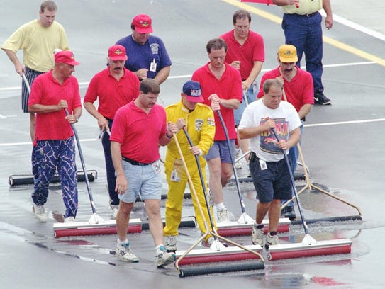 Workers squeegee water from the track at the exit of