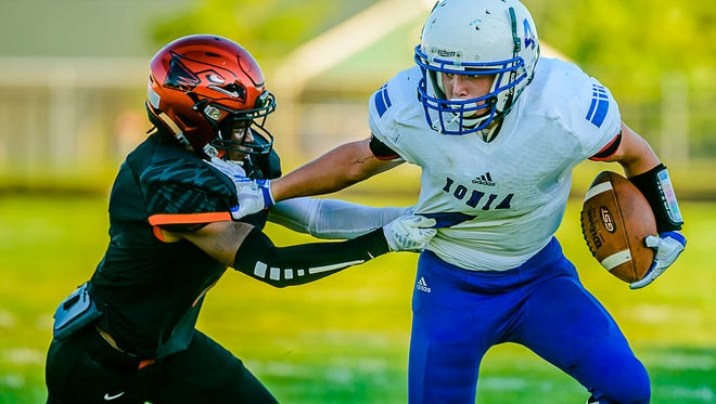Andrew Fox ,right, of Ionia is brought down by Michael Kemp of Charlotte after running for a 1st down in the 1st quarter of their season opening game Thursday August 25, 2016 in Charlotte.  KEVIN W. FOWLER PHOTO