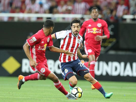 Rodolfo Pizarro de Chivas elude la marca de dos defensores