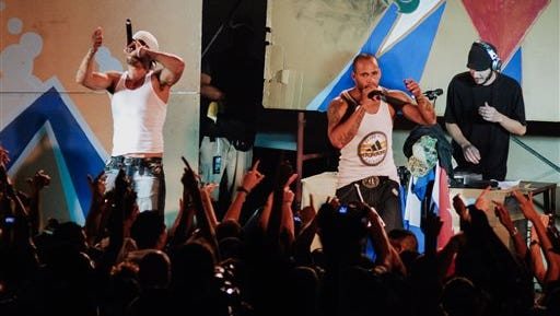 In this April 23, 2010, photo, members of Los Aldeanos, Aldo Rodriguez, left, and Bian Rodriguez, center, perform in concert at the Acapulco Theater in Havana, Cuba. Documents obtained by The Associated Press show that a U.S. agency infiltrated Cuba's hip-hop scene, recruiting unwitting rappers to spark a youth movement against the government.
