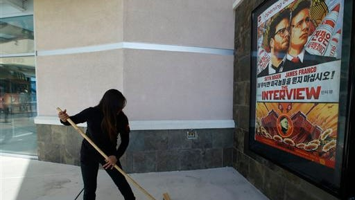 "A movie theater worker sweeps rain water under a poster for the movie ""The Interview"" at the AMC Glendora 12 movie theater, Wednesday, Dec. 17, 2014, in Glendora, Calif. The fallout from the Sony Pictures Entertainment hack that began four weeks ago exploded Tuesday after the shadowy group calling themselves Guardians of Peace escalated their attack beyond corporate espionage and threatened moviegoers with violence reminiscent of the terrorist attacks of September 11, 2001. (AP Photo/Damian Dovarganes)"
