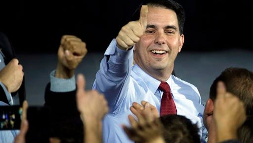 In this Nov. 4, 2014 file photo, Wisconsin Republican Gov. Scott Walker gives a thumbs-up after speaking at his campaign party, in West Allis, Wis. Walker defeated Democratic gubernatorial challenger Mary Burke. Walker said in an interview Monday, Dec. 29, 2014, that he remains committed to lowering property taxes next year as he promised in his re-election campaign, even though the state faces a projected $2.2 billion state budget shortfall that will likely result in spending cuts and other money-saving moves.  (AP Photo/Morry Gash, File)