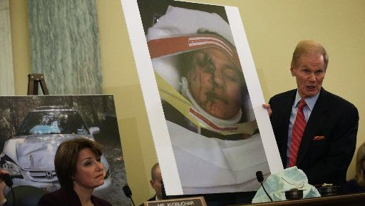 Sen. Bill Nelson (D-FL) (R) holds up a photo of Stephanie Erdman of Destin, Florida, of her face injury after an air bag explosion in her Honda Civic after a 2013 traffic accident. Sen. Amy Klobuchar (D-Minn. looks on during a Senate Commerce, Science and Transportation Committee hearing Nov. 20, 2014