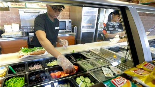 In this March 3, 2015 photo, workers make sandwiches at a Subway sandwich franchise in Seattle. The sandwich chain known for its marketing itself as a fresher alternative to hamburger chains on Thursday, June 4, 2015 told The Associated Press it will remove artificial flavors, colors and preservatives from its menu in North America by 2017. (AP Photo/Ted S. Warren)