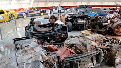 In this Wednesday, Aug. 12, 2015, photo, Wanda Cohen, of Roswell, Ga., takes a photo of the cars that were swallowed by the sinkhole at the National Corvette Museum in Bowling Green, Ky. The car-swallowing hole has been fixed but not forgotten at the museum. Yellow tape now marks the boundaries of the cavity that became a sensation and put the museum on the map. (AP Photo/Timothy D. Easley)