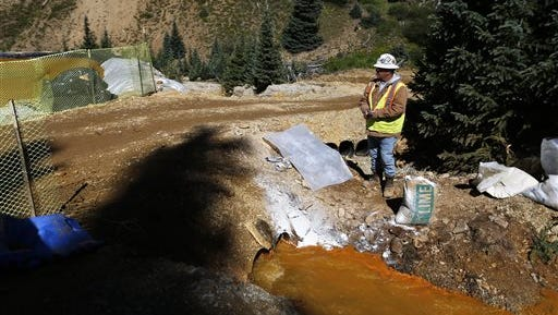 FILE - In this Aug. 14, 2015 file photo, an Environmental Protection Agency contractor keeps a bag of lime on hand to correct the PH of mine wastewater flowing into a series of sediment retention ponds, part of danger mitigation in the aftermath of the blowout at the site of the Gold King Mine, outside Silverton, Colo. Federal officials say they have suspended cleanup work and investigations covering 10 mining sites in four states to guard against a repeat of last month's massive wastewater spill from an inactive Colorado gold mine. Details provided to The Associated Press show the order applies to three sites in California, four in Colorado, two in Montana and one in Missouri. (AP Photo/Brennan Linsley, file)