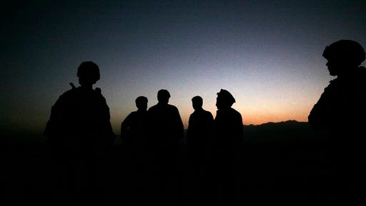 In this Oct. 18, 2009 file photo, U.S. Army soldiers stand with Afghan policemen before a joint patrol of Qalanderkhail, outside of Bagram Air Field in Afghanistan. An Afghan official says that a suicide bomber has killed three foreign troops in an attack on a joint Afghan-NATO foot patrol on Monday, Dec. 21, 2015. Mohammad Asim Asim, governor of Parwan province said an attacker on a motorcycle rammed a group of eight troops as they patrolled a village near Bagram Airfield, 45 kilometers (28 miles) north of Kabul.