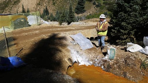 FILE - In this Aug. 14, 2015, file photo, an Environmental Protection Agency contractor keeps a bag of lime on hand to correct the pH of mine wastewater flowing into a series of sediment retention ponds, part of danger mitigation in the aftermath of the blowout at the site of the Gold King Mine, outside Silverton, Colo. EPA contractors released more than three million gallons of contaminated water Aug. 5 while working at the inactive mine site near Silverton. The EPA says it plans to return to Gold King Mine this spring or early summer to resume the preliminary cleanup work. (AP Photo/Brennan Linsley, File)
