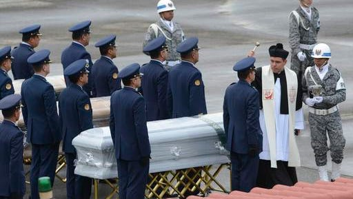 "A priest sprinkles ""holy water"" on a coffin containing the remains of a LaMia flight crew victim, at the military airbase in Rio Negro, Colombia, Friday, Dec. 2, 2016. An honor guard played taps early Friday as members of Colombia's military loaded the five flight crew victims of an air crash that also killed most members of a soccer team and a group of journalists, onto a cargo plane for the trip back to their native Bolivia."