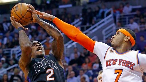 New York Knicks forward Carmelo Anthony (7) defends on a shot by Phoenix Suns guard Eric Bledsoe (2) during the second half of an NBA basketball game Tuesday, Dec. 13, 2016, in Phoenix. The Suns defeated the Knicks 113-111 in overtime.