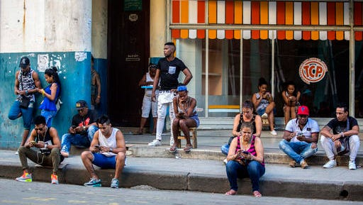 In this Jan. 6, 2017 photo, people use a public wifi hotspot in Havana, Cuba. Home internet came to Cuba in December 2016, in a limited pilot program that's part of the most dramatic change in daily life here since the declaration of detente with the United States on Dec. 17, 2014.