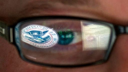 FILE - In this Sept. 30, 2011, file photo, a reflection of the Department of Homeland Security logo is seen reflected in the glasses of a cyber security analyst in the watch and warning center at the Department of Homeland Security's secretive cyber defense facility at Idaho National Laboratory in Idaho Falls, Idaho. Through history, the United States has relied on its borders and superior military might to protect against and deter foreign aggressors. But a lack of boundaries and any rulebook in cyberspace has increased the threat and leveled the playing field today.