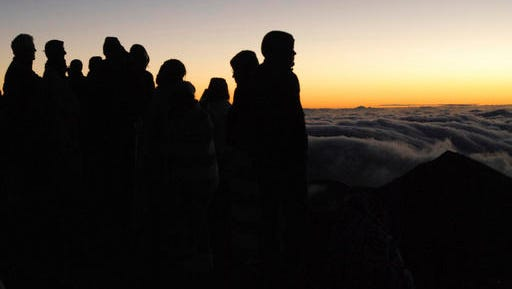 """People gather ahead of the sunrise on the summit of Haleakala volcano in Haleakala National Park on Hawaii's island of Maui, Sunday, Jan. 22, 2017. Mark Twain called the daily phenomenon the """"sublimest spectacle"""" he ever witnessed."""