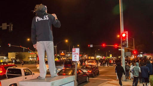 Protesters then took to Euclid Street, blocking traffic and marching north toward Ball Road, where they congregated in the intersection for several minutes in Anaheim, Calif., Wednesday, Feb. 22, 2017. A Los Angeles policeman is under investigation after a video appears to show him firing a single round during an off-duty tussle with a 13-year-old boy. No one was injured but two teenagers were arrested after the incident, which spurred dozens of people to protest against police Wednesday night in the streets of Anaheim, where the officer lives and the confrontation occurred.