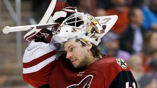 This March 22, 2016 photo shows Arizona Coyotes' Mike Smith putting his mask back on as he skates back to his position during the first period of an NHL hockey game against the Edmonton Oilers in Glendale, Ariz. When a collision knocked Smith's mask off, the Arizona Coyotes goaltender was less than pleased when he was told a few minutes later he had no choice but to leave the game. NHL general managers expected to talk about video review and concussion protocol for goaltenders at their annual March meeting. Coach's challenges for offside and goaltender interference will be on the docket at the GMs meeting in Boca Raton, Florida, this week.