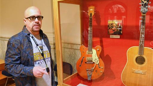 This file photo shows Memphis-based guitarist Robert Johnson standing by a display of guitars that belonged to Chet Atkins and Johnny Cash that he donated to the National Music Museum in Vermillion, S.D. Johnson also donated the guitar played by Elvis Presley during his final tour, but that may have to be taken off display. A lawsuit filed in July 2014 in South Dakota is seeking to determine who is the legal owner ofthe Elvis Presley guitar. A man now claims he is the owner of the slightly smashed acoustic guitar.