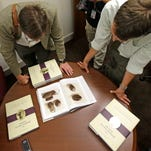 People look at pictures of the smooth, brown, egg-sized rock shown in the printer's manuscript of the Book of Mormon following a news conference Tuesday, Aug. 4, 2015, at the Church of Jesus Christ of Latter-day Saints Church History Library, in Salt Lake City. The Mormon church for the first time is publishing photos of a small sacred stone it believes founder Joseph Smith used to help translate the story that became the basis of the religion. The Mormon church is taking another step in its push to be more transparent, and is releasing more historical documents that shed light on how Joseph Smith formed the religion.