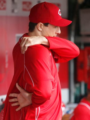 Cincinnati Reds starting pitcher Homer Bailey (34) stretches his arm out in the dugout in the seventh inning during the MLB game between the Cincinnati Reds and the St. Louis Cardinals, Thursday, Aug. 6, 2015.