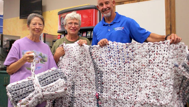 From left, Sharron Denison, Susan Schiffner and Mark Schultze display a completed plastic bag mattress pad. The pads are constructed from recycled plastic bags and will be distributed to homeless citizens as an alternative form of padding and insulation.